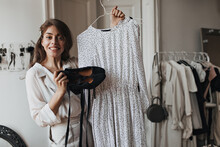 Happy Woman Holding Black Shoes And Polka Dot Dress. Cheerful Young Lady In Beige Blouse And Pants Smiles Widely In White Room