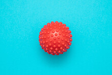 Closeup Shot Of A Red Spiky Massage Ball Isolated On Blue Background
