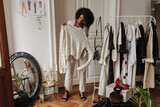 Stylish young dark-skinned curly lady in beige pants and jacket smiles, poses in dressing room an holds hanger with trendy knitted sweater.