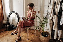 Charming Cute Short-haired Woman In Stylish Linen Red Dress Sits On Chair In Cozy Light Room, Holds Computer Tablet And Smiles.