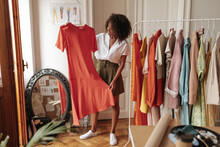 Curly Stylish Dark-skinned Woman In Khaki Shorts And White Blouse Holds Hanger With Long Red Dress And Poses In Dressing Room.