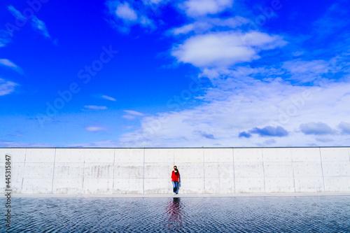 Fototapeta 白い壁と青空と女性