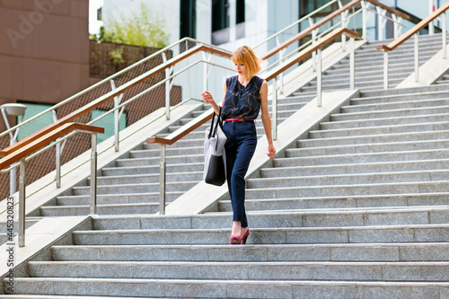 Canvas Elegant fashionable woman descending exterior steps in town