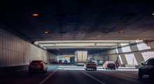 Cars And A Motorcycle Are Driving In The Tunnel Under The Road