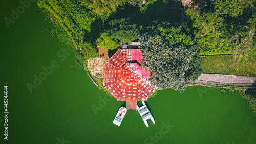 Foto Aerial view of a beautiful red boathouse with two boats on the side of a lake