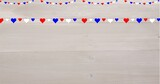 Digitally generated image of red and blue heart shaped hanging decorations against wooden background