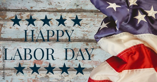 Digitally generated image of american flag and happy labor day text against wooden background