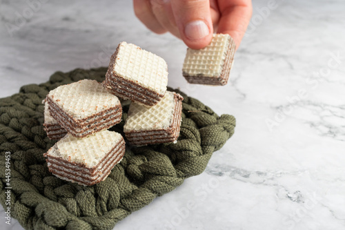 Foto Closeup of a hand picking up square wafer biscuits with chocolate cream