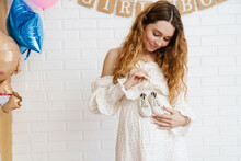 Happy Young Pregnant Woman Holding Small Baby Shoes