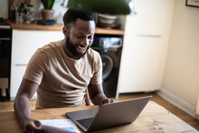African American Male Online Banking At Home In Kitchen