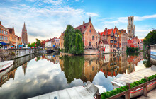 Belgium - Historical Centre Of  Bruges River View. Old Brugge Buildings Reflecting In Water Canal.