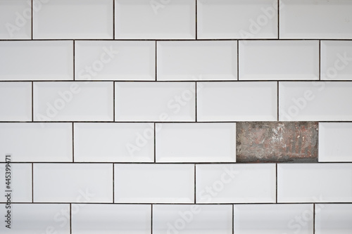 Billede på lærred Hole on ceramic white tile wall. One missed tile on wall.