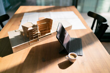 Laptop With Coffee Cup And Architectural Model On Table At Office