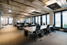 Chairs Arranged At Desk In Modern Office