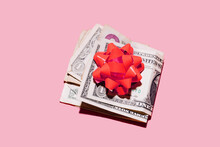 Studio Shot Of Folded Dollar Bills With Red Gift Bow