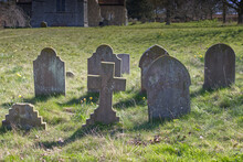 Old Grave Stones In Churchyard In England Amongst Green Grass.