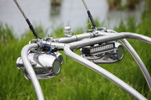 Close Up Chrome Tower Boat Targa Top With Speakers, A Pole For Towing Water-skiing On A Motor Boat For Wake Riding At Summer Day Against Green Grass And Water Background, Outdoor Watersports Activity