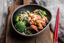 Sesame Fried Chicken With Broccoli Garnished With Sriracha Sauce In Bowl