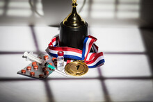 Gold Medal And Champion's Cup, Syringe With Doping Substance, Pill Tablet And Vial With Prohibited Substance With Lights And Shadows Of A Curtain Entering Through The Window. Sport And Doping Concept