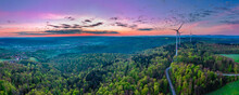 Germany, Baden Wurttemberg, Aerial View Of Swabian Forest With Wind Turbines Along Road At Sunrise
