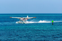 Seaplane Landing In The Boat Channel Bringing Guests To A Remote Island For A Day Of Beach Recreation.