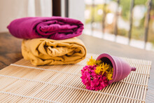 Menstrual Cup With Flowers On Bamboo Mat By Colored Clothes