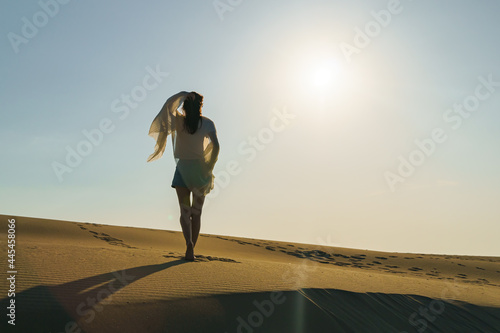 Fototapeta Millennial Woman standing on wavy sand dunes in desert landscape at golden sunset light and wind