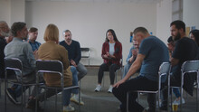 People Supporting Upset Man During Group Meeting