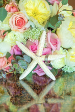 Closeup Of Bridal Bouquet With Wedding Rings On Starfish.