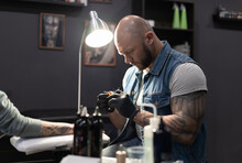 Tattoo Artist Working With Client