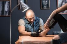 Bald Man Making Tattoo On Foot Of Woman