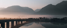 Long Bridge Over The Calm Clear River Surrounded By Greenery-covered Hills During The Sunrise