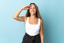 Young Blonde Woman Isolated On Blue Background Saluting With Hand With Happy Expression