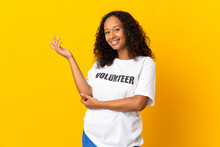 Teenager Cuban Volunteer Girl Isolated On Yellow Background Extending Hands To The Side For Inviting To Come