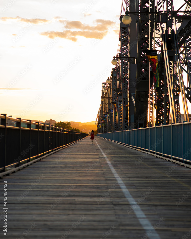 Unique wallpaper with a woman walking on a huge empty bridge under a bright sky at sunset