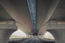 Underside Of A Huge Bridge With Empty Dry Fields Surrounding It On A Sunny Day