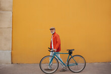 Full Length Shot Of Man In Cap And Orange Jacket Walking With Bicycle. Bright Adult In Jeans And White T-shirt Is Looking At Camera Against Yellow Wall..