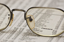 Reading Glasses On A Newspaper Focusing On The Finance Heading In The Financial Section