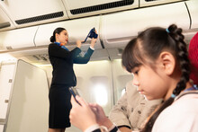 Low Angle Side View Of Asian Female Flight Attendant Standing Does The In-flight Safety Demonstration To Passengers On A Flight With Blurred Of Asian Little Girl Playing A Cell Phone In The Foreground