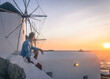 mężczyzna przy wiatraku patrzy na zachód słońca