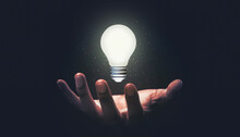 Hand Hold Glowing Idea Light Bulb And Innovation Thinking Creative Concept On Success Inspiration Dark Background With Solution Creative Business Design.
