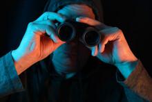 Middle-aged Man, Stalker In Hood Looks Through Black Binoculars In Dark, Peeps, Illegally Tracks Down Personal Secrets Of Neighbors, Concept Of Industrial Espionage, Surveillance