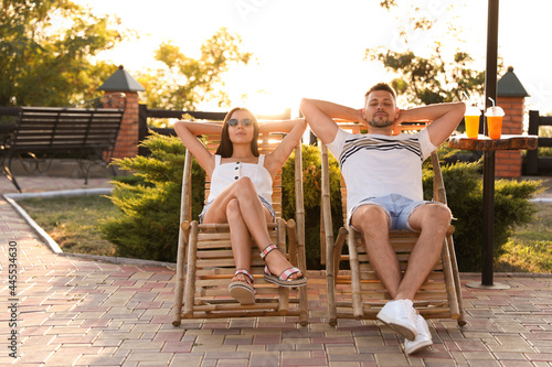 Couple resting together in deck chairs outdoors Fototapet