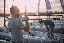 Tourist Walks On Sailing Yachts. Male Tourist On Vacation On A Boat At The Sea.