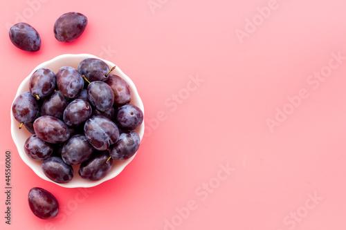Fotografie, Obraz Purple plums in bowl. Plum harvest top view