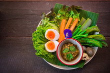 """Northern Thai Green Chili Dip Or Call In Thai Is """"Nam Prik Num"""" Food Of Thai Tradition Eat With Pork Crackling Or Fresh Vegetables On A Banana Leaf With A Wooden Floor Background."""
