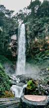 A Very Tall Waterfall And Has Greenery Around It