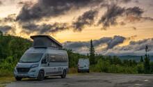 Two Camper Vans Parked In The Wilderness Of Northern Sweden Under A Colorful Sunset Sky