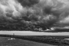 Grayscale Shot Of A Brewing Storm In The Countryside With Enormous Gloomy Clouds Over A Hill