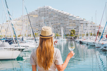 Blonde Hair Woman In A Hat Standing With Her Back On Sea, Yachts, Buildings And Boats Background. White Wine Glass In Hand. Vacation In Europe. Nice, French Riviera. Travel Photo.